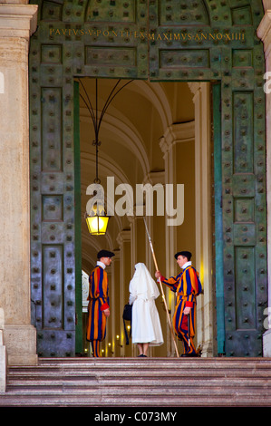 Nun walks through entrance to the Vatican between guards of the Swiss army in traditional uniforms, Rome, Lazio, - Stock Photo
