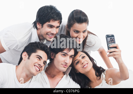 Friends taking picture of themselves with a mobile phone - Stock Photo