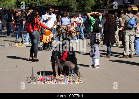 black african migrant man selling eiffel towers souvenirs and curios infront of eiffel towers,paris,france,europe - Stock Photo