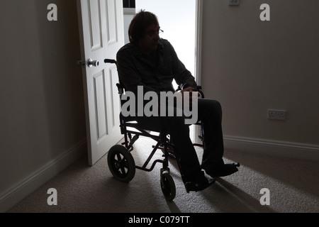 Man in wheelchair, sitting alone in a dark room. - Stock Photo