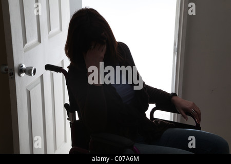Woman in wheelchair, hand covering her face. - Stock Photo