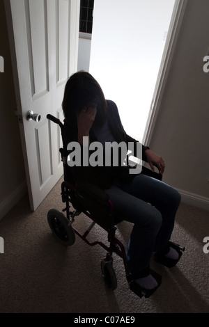Woman in a wheelchair with hand to her head. - Stock Photo