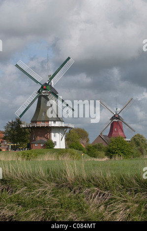 Twin Mills of Greetsiel, in front of a sky with dark clouds, Krummhoern, East Frisia, Lower Saxony, Germany, Europe - Stock Photo