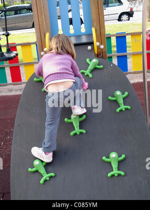 Three and a half year old child on climbing board in playground - Stock Photo