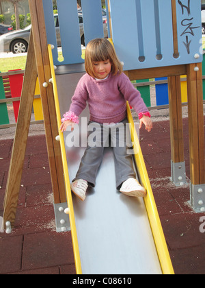 Three and a half year old child on slippery slide in playground - Stock Photo