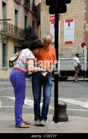 Two tourists look at a map and lean on a lamp post. - Stock Photo