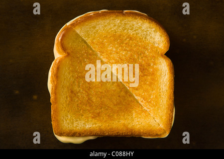 A Grilled Cheese Sandwich cut in half diagonally pulling the cheese on a wood table - Stock Photo