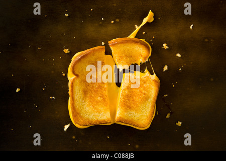 A Grilled Cheese Sandwich cut in half and with the top right corner broken off pulling the cheese on a wood table - Stock Photo