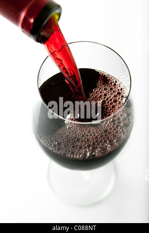 A glass of Red Wine being poured from the bottle on a white background. - Stock Photo