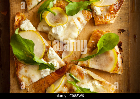 Thin and crispy crust Pizza with Mozzarella, Goat Cheese, Fig Spread, Pear and Arugula prepared by Gianni Scappin, - Stock Photo