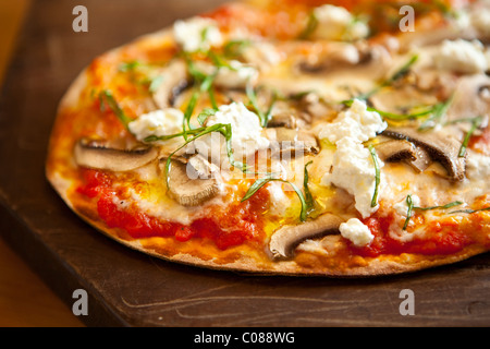Thin and crispy crust Pizza with Mozzarella, Mushrooms, Goat Cheese and Basil prepared by Gianni Scappin, Chef/Owner - Stock Photo