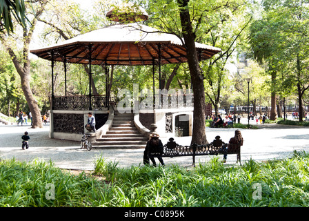 charming old 19th century bandstand amid greenery of Chapultepec Park with elaborate cast iron frame & wood roof - Stock Photo