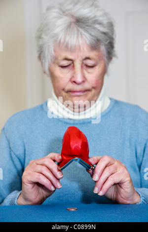 Poor senior elderly woman pensioner on small state pension with no money and a sad expression emptying a penny coin - Stock Photo