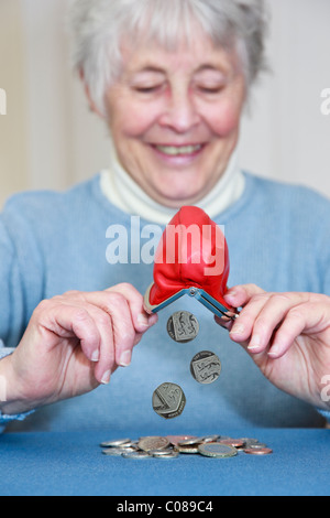Composite of a wealthy senior elderly pensioner OAP lady retiree with a pleased expression emptying a pile of money - Stock Photo