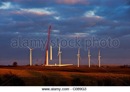 A large crane lifts part of the base assembly of a wind turbine under construction in a central Iowa wind farm. - Stock Photo