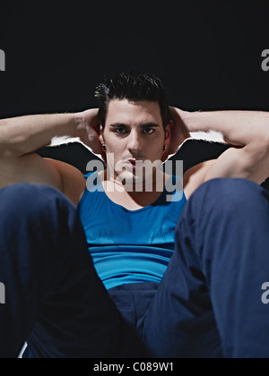 young adult caucasian male in blue sportswear exercising abdominals on black background, looking at camera. - Stock Photo