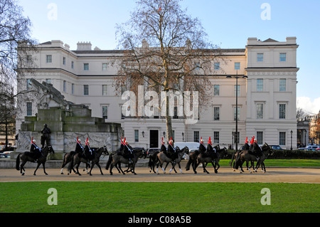 Household Cavalry horses & troopers passing Lanesborough Hotel 5 stars expensive luxury hotel on blue sky day winter - Stock Photo