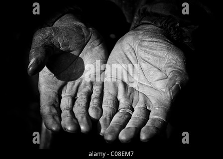 An elderly farmer's hands outstretched showing years of hard work. - Stock Photo