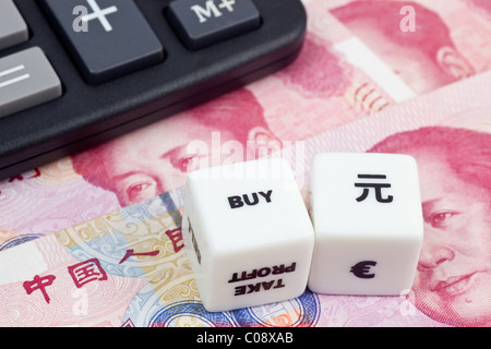Chinese currency with calculator and dice - Stock Photo