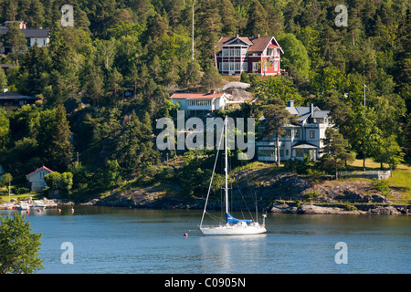 A lone sailboat is at anchor or on a mooring in a picturesque cove in the archipelago near Stockholm, Sweden. - Stock Photo