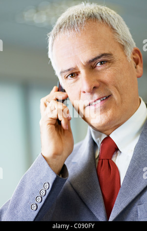 portrait of mature business man talking on the phone, looking at camera and smiling. - Stock Photo