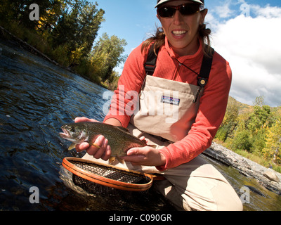 Woman holds and shows off a Rainbow Trout caught while fly fishing on the Russian River, Kenai Peninsula, Southcentral - Stock Photo