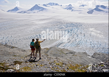 Man and woman enjoy view overlooking Harding Icefield, Kenai Fjords National Park, Kenai Peninsula, Southcentral - Stock Photo