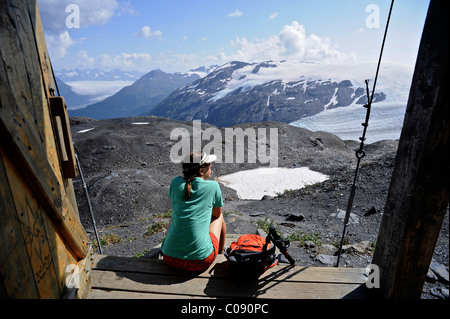 Female backpacker enjoys the view from an alpine hut along the Harding Icefield trail, Kenai Fjords National Park, - Stock Photo