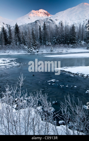 First light strikes a peak in Portage Valley, Chugach National Forest, Southcentral Alaska, Winter - Stock Photo