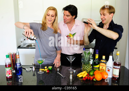Friends at the bar mixing drinks - Stock Photo