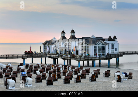 Beach chairs on the sandy beach of the Baltic resort Sellin, in the back the historic pier with restaurant, Ruegen - Stock Photo