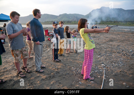 Young girl shoots a pistol in her pajamas and flip-flops at the edge of the Yukon River, Yukon-Charley Rivers National - Stock Photo