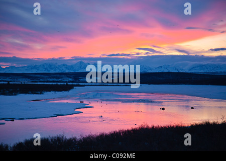 View of sunset reflected in Summit Lake with Alaska Range in the background, Paxon, Southcentral Alaska, Spring - Stock Photo