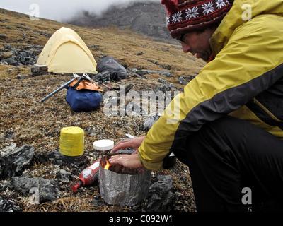 Backpacker prepares food at camp below Mt. Chamberlin, Brooks Range, ANWR, Arctic Alaska, Summer - Stock Photo