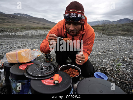 Backpacker prepares food base camp along the Hulahula River, Brooks Range, ANWR, Arctic Alaska, Summer - Stock Photo