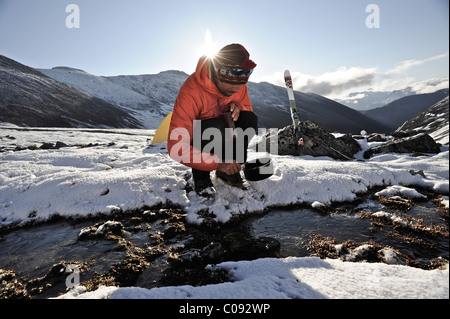 Backpacker fills pan with water from a creek at an alpine camp below Mt. Chamberlin, Brooks Range, ANWR, Arctic - Stock Photo
