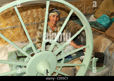 Silk production, Usbek woman spinning silk threads, Silk Road, Fergana Valley, Uzbekistan, Central Asia - Stock Photo