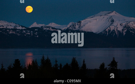 View of a full moon rising over Kachemak Bay near Homer, Kenai Peninsula, Southcentral Alaska, Spring - Stock Photo