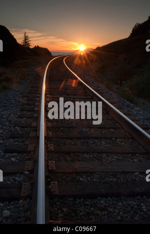 The setting summer sun reflects on train rails near Beluga Point along Turnagain Arm, Southcentral Alaska, Summer - Stock Photo