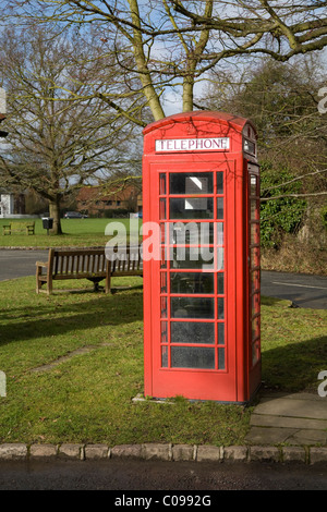 An original red telephone / coin operated phone call box on a grass verge, near a park bench, in Holyport, Berkshire. - Stock Photo
