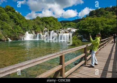 Tourist photographing a waterfall from a wooden bridge, Krka National Park, aeibenik-Knin County, Croatia, Europe - Stock Photo