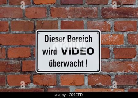 Sign on brick wall, 'Dieser Bereich wird VIDEO ueberwacht!', German for 'this area is under video surveillance' - Stock Photo