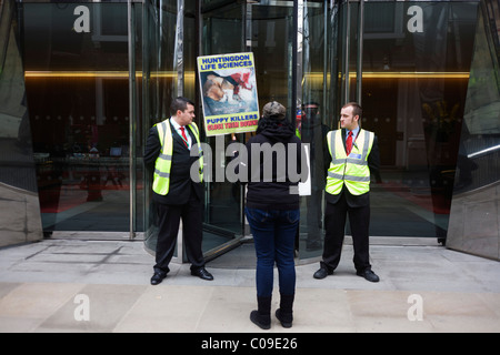 A lone animal Rights protester stands outside the offices of the French Axa Insurance company. - Stock Photo