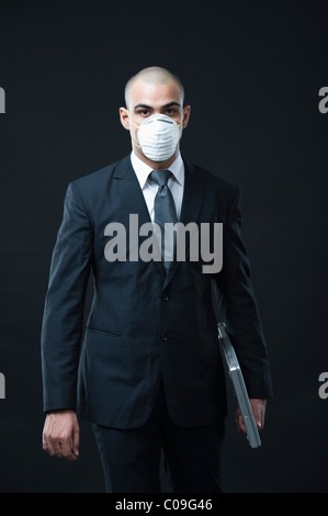 Businessman wearing a pollution mask and holding a laptop - Stock Photo