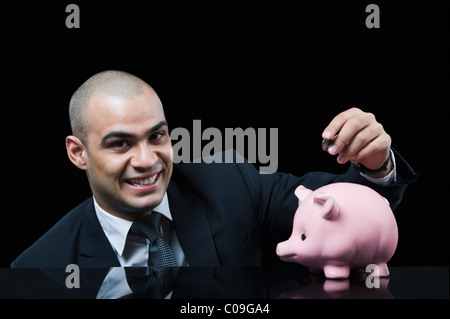 Businessman inserting a coin into a piggy bank - Stock Photo