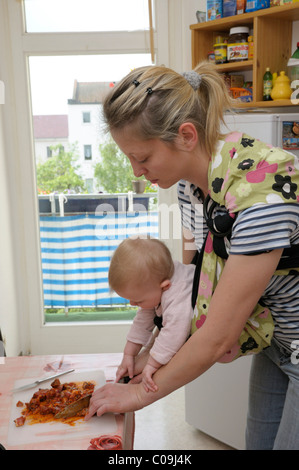 Young woman, 29, with a girl, eight months, in the kitchen - Stock Photo