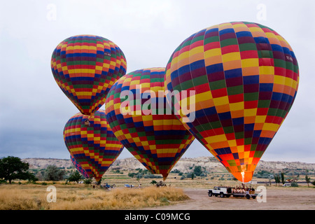 Hot air balloon being prepared for a flight over the tufa landscape of the UNESCO World Heritage Site Goreme, Cappadocia - Stock Photo
