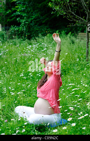 Pregnant woman in a garden, stretching, doing back exercises - Stock Photo