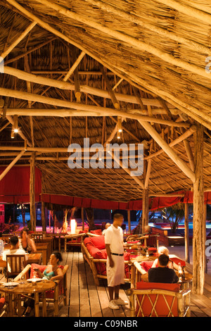 The inside of a thatch restaurant at a beach resort. - Stock Photo