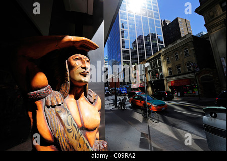 Carved Indian figure looking at the hustle and bustle of the busy Yonge Street, Toronto, Ontario, Canada - Stock Photo